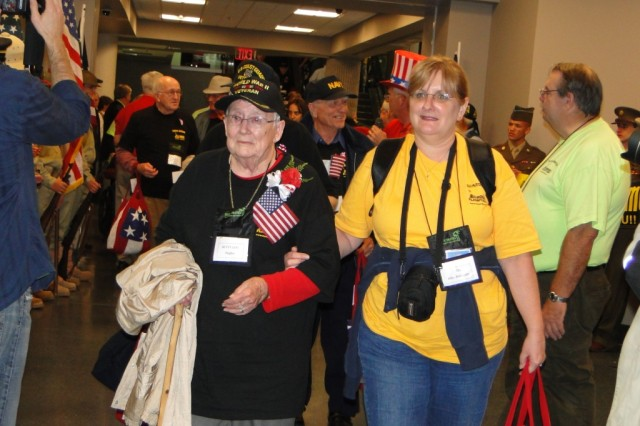 WW II veteran Betty Lou Trimble Hughes walks with an Honor Flight guardian into the waiting area of the Huntsville International Airport in anticipation of seeing her family. She traveled on Honor Flight with her brother, WW II veteran Walter Trimble. She was one of two female WW II veterans to make the Oct. 24 flight.