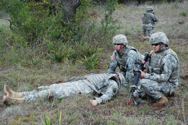 """Soldiers of the 201st Military Intelligence Battalion retrieve a """"casualty"""" while under simulated sniper attack in an exercise on reacting to direct fire. Battalion members completed field training exercises in spite of intermittent rain at Camp Bullis, Texas, Sept. 24. (U.S. Army photo by Spc. Natalie Sampson)"""
