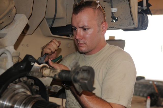 091008-A-6758N-004 - Spc. Don Kleitz, a mechanic with the 443rd Transportation Company, an Army Reserve unit based out of Lincoln, Neb., works on a vehicle at the unit's machine shop located at Camp Arifjan, Kuwait on October 9, 2009.