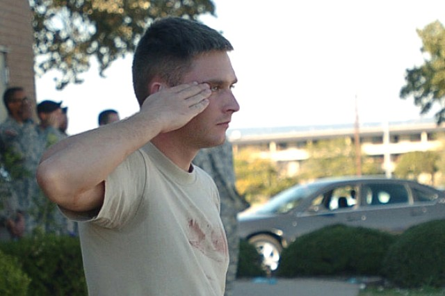 A first responder to a lone gunman's attack at Fort Hood, Texas, Nov. 5, 2009, renders honors at retreat after aiding his fellow Soldiers.
