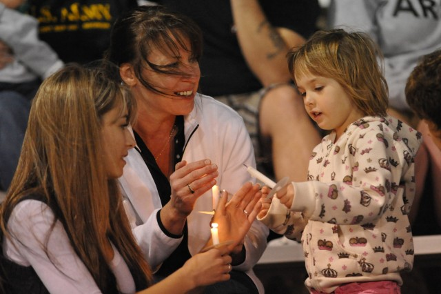 Jamie Anderson holds a candle for her daughter, as her grandmother, Jo Ellen Freleigh, of New York, protects her candle from the wind at Fort Hood, Texas. About 300 people attended a candlelight prayer vigil held Nov. 6, at Hood Stadium to honor those who were killed and wounded Nov. 5, when a lone gunman opened fire in the Soldier Readiness Processing Center on post.