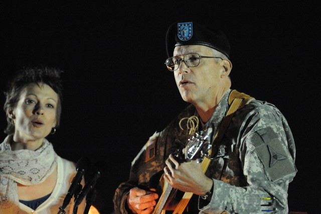 Chaplain (Col.) Mike Lembke, III Corps, plays guitar leading mourners in song during a candlelight vigil held to commemorate Soldiers and civilians killed and wounded Nov. 5, by a lone gunman inside and near the Fort Hood, Texas, Soldier Readiness Processing Center.