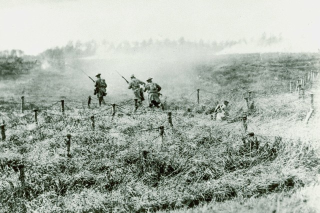 Into the Valley of Death: World War I  (men crossing No Man's Land).  107th Infantry Regiment personnel advancing through barbed wire near Beauquesnes, Somme, on Sept. 13, 1918. (WWI Signal Corps Photograph Collection)