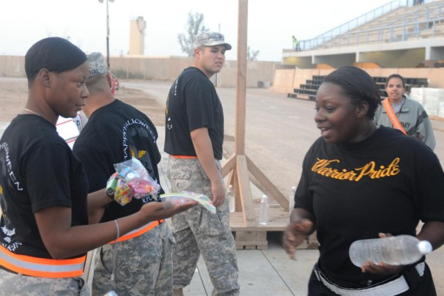 Spc. Rolonda Green, shop office clerk with the 699th Maintenance Company, hands out candy to one of the participants in the Halloween 5K fun run Oct. 31 at Holt Stadium at Joint Base Balad, Iraq. Green, a Hopkins, S.C., native, received the candy from the unit's Family Readiness Group back at Fort Irwin, Calif.