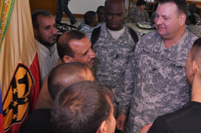 Col. Larry Phelps, commander of the 15th Sustainment Brigade, and Command Sgt. Maj. Nathaniel Bartee, the 15th Sust. Bde. senior noncommissioned officer, speak with Iraqi workers from the Al-Qayyarah pump house at a luncheon in their honor Nov. 3 at the dining facility at Contingency Operating Location Q-West, Iraq.