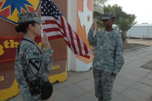 Cpt. L. Pilar Restrepo, commander of Headquarters and Headquarters Company, 13th Sustainment Command (Expeditionary), administers the oath of enlistment to Staff Sgt. Michelle Batiste, a material supply noncommissioned officer with the  13th ESC, during a ceremony Nov. 2 here at Joint Base Balad, Iraq. Batiste said she re-enlisted to take care of her children.