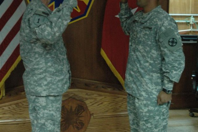 Brig Gen. Paul L. Wentz, commanding general of the 13th Sustainment Command (Expeditionary), administers the oath of enlistment to Sgt. Jose Graulau, executive assistant with the 13th ESC. Graulau said he was not going to re-enlist but a talk with his brother, who is also deployed in support of contingency operations here in Iraq, changed his mind.