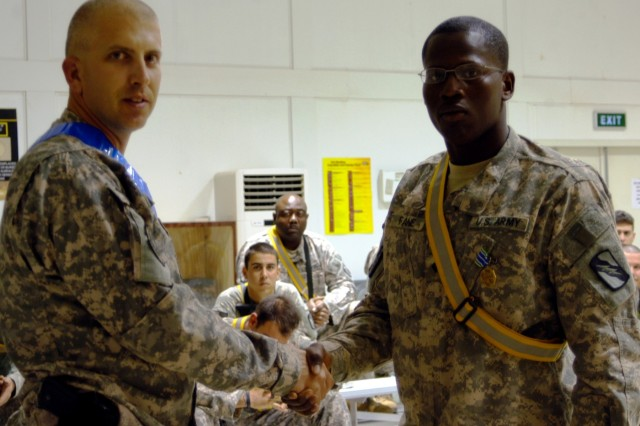 CONTINGENCY OPERATING LOCATION Q-WEST, Iraq - Lt. Col. Kerry Goodman (left), a Hattiesburg, Miss., native and commander of 2nd Battalion, 198th Combined Arms headquartered in Senatobia, Miss., awards an Army Achievement Medal to Spc. Corderal Fane, a Tallahatchie, Miss., native and gunner with 1st Platoon, C Company, 2/198th CAB out of Oxford, Miss., at the Q-West Convoy Readiness Center Convoy, Oct. 28. Fane and his platoon mates were attending a briefing before a mission to Forward Operating Base Warrior.