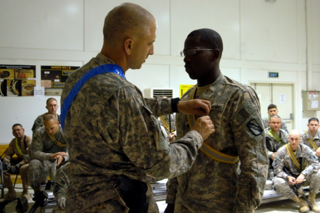 CONTINGENCY OPERATING LOCATION Q-WEST, Iraq - Lt. Col. Kerry Goodman (left), a Hattiesburg, Miss., native and commander of 2nd Battalion, 198th Combined Arms headquartered in Senatobia, Miss., pins an Army Achievement Medal on Spc. Corderal Fane, a Tallahatchie, Miss., native and gunner with 1st Platoon, C Company, 2/198th CAB out of Oxford, Miss., at the Q-West Convoy Readiness Center Convoy, Oct. 28. Fane and his platoon mates were attending a briefing before a mission to Forward Operating Base Warrior.