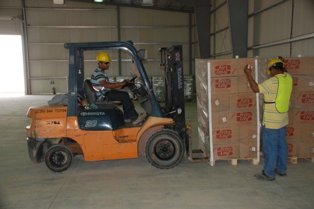 Civilian contractors move some of the first pallets of food into the new Class I supply warehouse on Contingency Operating Base Speicher Oct. 31. (Courtesy photo)