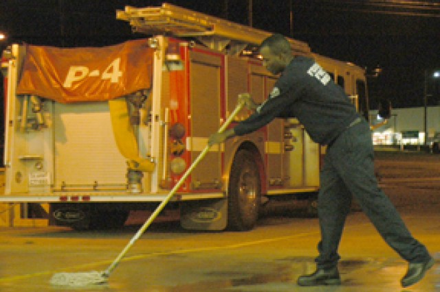 Firefighter Lontae Bell mops the garage at Fire Station No. 1 during morning chores Oct. 21.