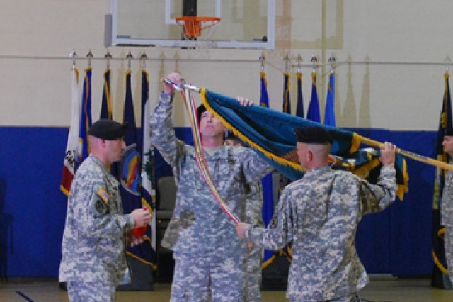 Lt. Col. Blace Albert, commander of the 4th BSTB, and Command Sgt. Maj. Dale Van Ormer, command sergeant major for 4th BTSB, pin the meritorious unit award onto the 4th BSTB's colors.
