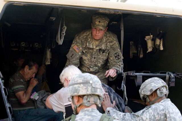 Spc. Brian Peterson, a medic, helps a victim into the back of an Army ambulance during the national emergency response exercise -- Vibrant Response -- at Muscatatuck Urban Training Center in Butlerville, Ind., Nov. 8.
