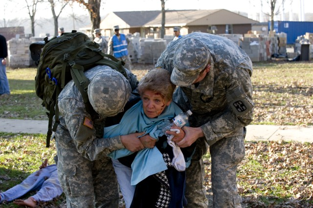 A role player grieving over her husband is helped to an Army ambulance during the national emergency response exercise -- Vibrant Response -- at Muscatatuck Urban Training Center in Butlerville, Ind.,  Nov. 9.