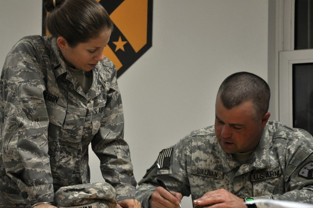 Airforce 1st Lt. Augusta Fehn, defense contract manager and Las Vegas native, helps a Functional Academic Skills Training student with a math problem at the newly reopened education center here, Nov. 5. (U.S. Army photo by Sgt. Matthew C. Cooley, 15th Sustainment Brigade public affairs)