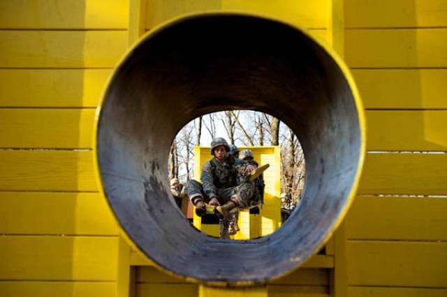 A North Georgia College and State University Team 1 Cadet balances precariously on a beam while trying to construct a bridge to the end of the Leadership Reaction Course, through the tunnel, during the 1st Brigade Bold Leader Challenge at Fort Knox.""