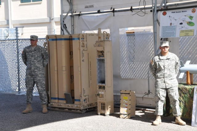 Sgt. Luke Francis and Sgt. Sam Lazdowski stand ready in front of the launcher to brief BGen. Prittard on the Non Line-of-Sight Launch System (NLOS-LS).