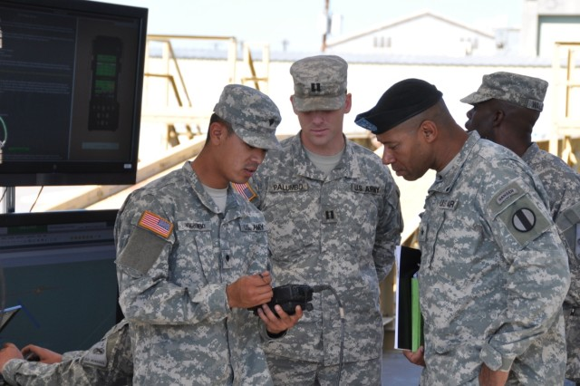 Spc. James Vongbounemy of the AETF Fires battalion demonstrates the manual firing procedure for the Non Line-of-Sight Launch System (NLOS-LS) for BGen. Pittard while Cpt. Jonathan Palumbo observes.
