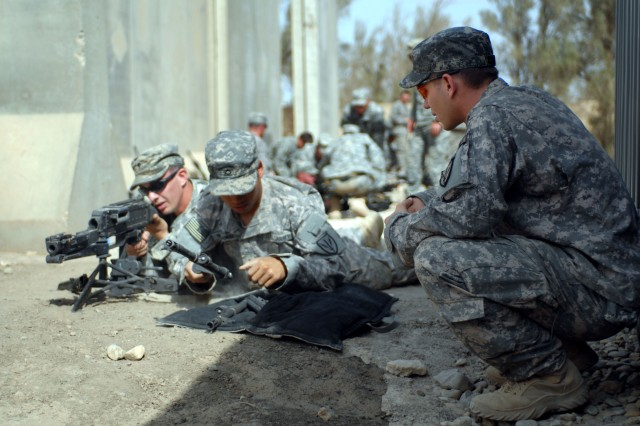 Sgt. Sean Gray (far right) observes as Pfc. Khonesvanh Thephavongsa (center) prepares to change the barrel of a M240 machine gun while Spc. Joseph Stout lays suppressive fire during team training at Contingency Operating Base Adder, Tallil, Iraq, Nov. 6. The Soldiers are with Company C, 38th Long Range Surveillance, 201st Battlefield Surveillance Brigade out for Fort Lewis, Wash., and will help train Iraqi Security Force soldiers on proper surveillance and intelligence gathering techniques.