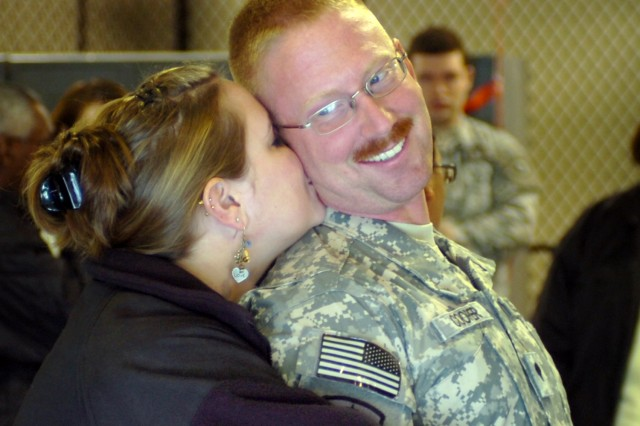 MARTINSBURG, W.V. - Spc. Cooper of the 351st Ordnance Company, 2nd platoon looks back at his wife as she gives him a hug and kiss inside the United States Army Reserve Center here Thursday. The platoon had been deployed to Iraq for 10 months.