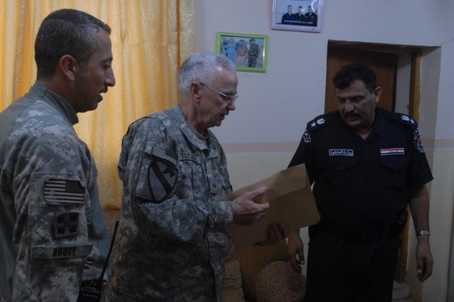 J. Tucker, a law enforcement professional working with the U.S. Army, shares evidence with Lt. Col. Fitaah, the police chief of a station in Hawijah, Iraq, during a meeting at Fitaah's station Nov. 5. Both the U.S Army and the Iraqi Police regular share intelligence and evidence with one another.