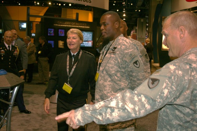 Gen.  Ann Dunwoody, commanding general of Army Materiel Command, and Maj. Gen. Yves J. Fontaine, commanding general of Army Sustainment Command, converse with Master Sgt. Alton Lewis on ASC's new portal exhibit at the AUSA meeting. Lewis served as a subject matter expert for ASC.