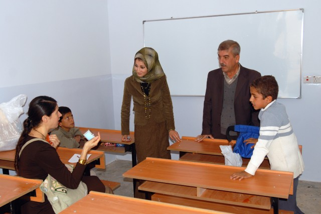 Kirkuk's Provincial Reconstruction Team Public Diplomacy Officer Stacy Barrios (seated left) speaks with teachers and students during the opening of the new Chemin Primary School in Kirkuk province, Iraq, Nov. 3. The project was a combined initiative between the Kirkuk PRT, the Director General of Education, and U.S. forces in Iraq, in an effort to improve the educational infrastructure and environment in Kirkuk province