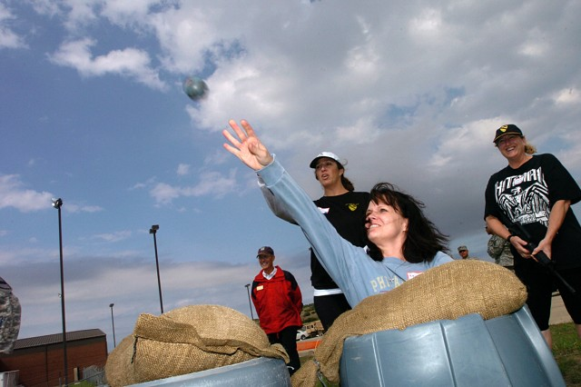 Kelly Armstrong chucks a grenade at a target as Karen Maxton (left) and LeAnn Volesky look on during the Greywolf Spouses' Spur Ride Oct. 29, on Fort Hood, hosted by the 3rd Brigade Combat Team, 1st Cavalry Division.