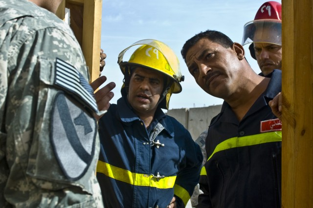 BAGHDAD - Iraqi firefighters from the 29th Center for Defense listen intently to Cpl. John Curtis, a combat medic and former firefighter from Lisbon, Maine, during joint-firefighter training at Joint Security Station Ur in northern Baghdad, Nov. 8.