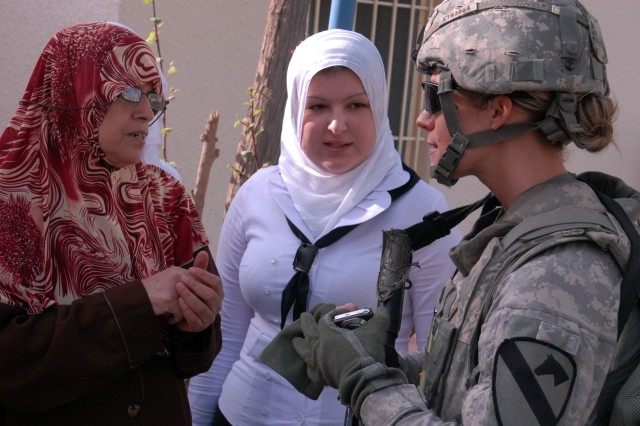 BAGHDAD - First Lt. Lacey Rector (right), from Willoughby Hills, Ohio, talks with students and teachers at the reopening ceremony for the Shab Female School, here, Nov. 5.