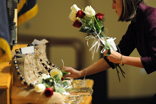 An unidentified woman places roses on Soldier boots during a memorial service on Fort Lewis, Wash., Nov. 10. Staff Sgt. Luis M. Gonzalez, of South Ozone Park, N.Y.; Sgt. Fernando Delarosa, of Alamo, Texas; Sgt. Dale R. Griffin, of Terre Haute, Ind.; Sgt. Issac B. Jackson, of Plattsburg, Mo.; Sgt. Patrick O. Williamson, of Broussard, La.; Spc. Jared D. Stanker, of Evergreen Park, Ill., and Pfc. Ian Walz, of Vancouver, Wash., all with 1-17 Inf., 5th Bde., 2nd Inf. Div., were killed when an IED destroyed their Stryker vehicle in Afghanistan, Oct. 27.