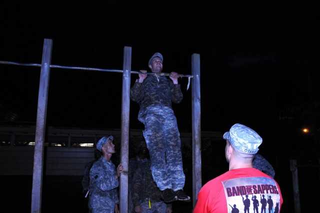1st Sgt. Bryan Otero, first sergeant, 34th Sapper Company, watches on as a Soldier helps his team with the 80 pull-ups challenge during the Super Sapper Competition Nov. 5 at Schofield Barracks.
