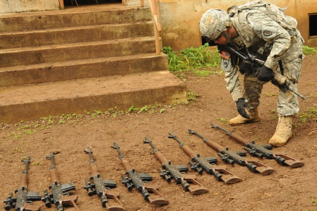 A Soldier from the 728th Military Police Battalion lays out weapons recovered from a house during forensic material gathering Nov. 5 at Schofield Barracks.