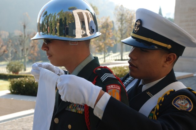 A Naval Junior Reserve Officer Training cadet helps his Army JROTC color guard counterpart get ready for the Veterans Day ceremony at the Florence American Cemetery Nov. 11.