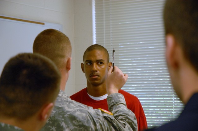 Sgt. 1st Class Len Taylor tries to watch a pen being moved back and forth as part of a field sobriety test called the Horizontal Gaze Nystagmus test. Taylor volunteered to drink alcohol so that police officers taking a weeklong training course could practice making alcohol-related traffic stops.
