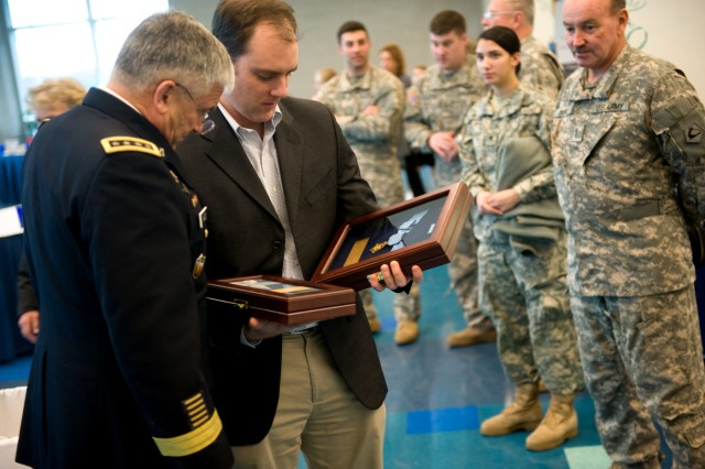 Army Chief of Staff Gen. George W. Casey Jr. takes a close look at the Medal of Honor that was posthumously awarded to Sgt. 1st Class Jared C. Monti while at a Veterans Day reception in Buzzards Bay, Mass., Nov. 11, 2009.