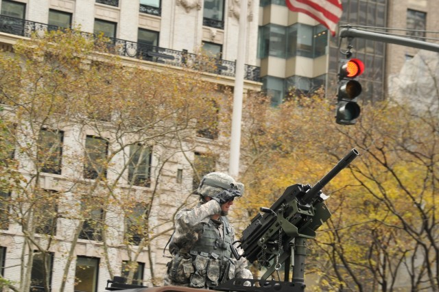 """A humvee gunner from the famous """"Fighting 69th"""", the 1st Battalion 69th Infantry of the New York Army National Guard, salutes the reviewing stand on Wednesday, Nov. 11, as the massive New York City Veterans Parade made its way up 5th Avenue. 1,500 members of the New York Army National Guard took part in the annual salute to veterans. This year\'s parade was one of the largest ever."""