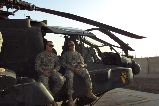 SPC Wood, left, and 1SG Montanez hang out on the AH-64 helicopter after SPC Wood re-enlisted for 6 years, receiving a $4800 bonus and his duty station of choice, Fort Stewart, GA.