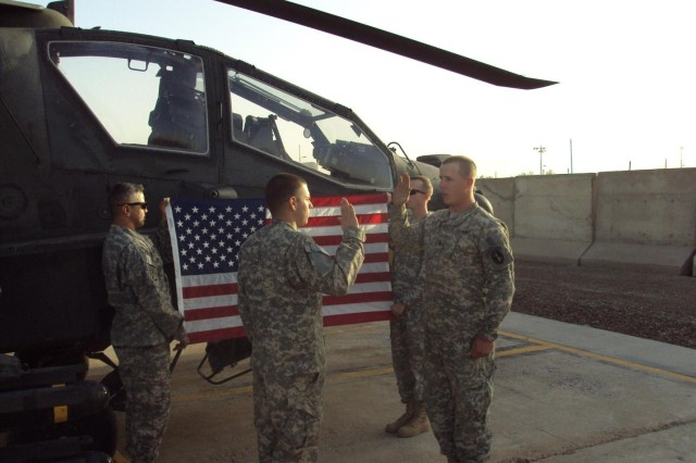 SPC Wood re-enlists in front of an AH-64 Helicopter on the airfield at Camp Taji, Iraq. SPC Wood re-enlisted to take care of his wife and his son.