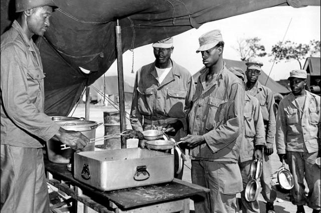 SFC Arnold S. Scales (Richmond, VA) serves steak at the 43rd Transportation Truck Company, 8th U.S. Army, near Uijongbu, Korea 18 June 1951.