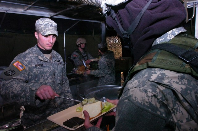 ALTOONA, Pa. -- Sgt. Jonathan Odrosky, of Houtzdale, Pa., a food service specialist with the 298th Maintenance Company here, serves lunch to a fellow soldier during the Philip A. Connelly competition for Field Kitchen at Fort Roberdeau, Pa., Nov. 7. The 298th MC Co. cooks were required to cook a specific menu as part of the competition.