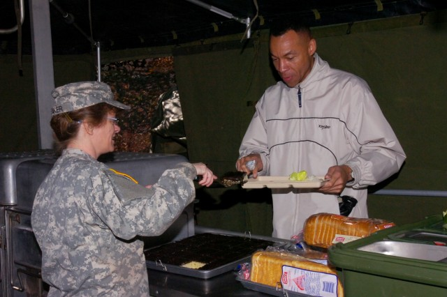 ATLOONA, Pa. -- Spc. Katherine Baker, of Altoona, Pa., a food service specialist with the 298th Maintenance Company here, serves the first meal to Alfred Rudolph, IFSEA evaluator and Secretary of the Navy's Executive Dining Facility, during the Philip A. Connelly competition for Field Kitchen at Fort Roberdeau, Pa., Nov. 7.