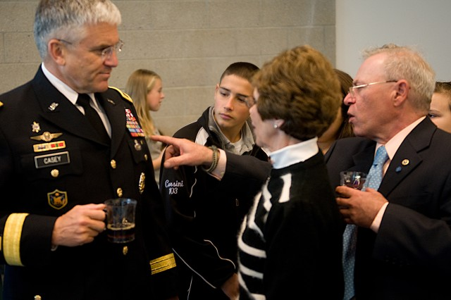 Paul Monti, father of Medal of Honor recipient Sgt. 1st Class Jared C. Monti, explains some of the Army's medals to his family with the help of Army Chief of Staff Gen. George W. Casey Jr., at a Veterans Day reception in Buzzards Bay, Mass., Nov. 11.