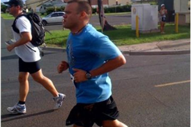 Army CPT Ray O'Donnell, right, and civilian physical therapist, David Newman run towards Hanger 103 at Marine Corps Base Hawaii on their way to the finish line.
