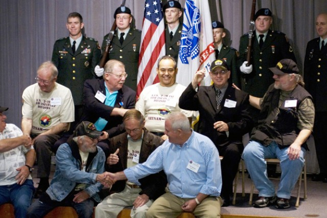 Veterans from the 9th Infantry Division shake hands during a group photo at the Monterey History and Maritime Museum Oct. 27.
