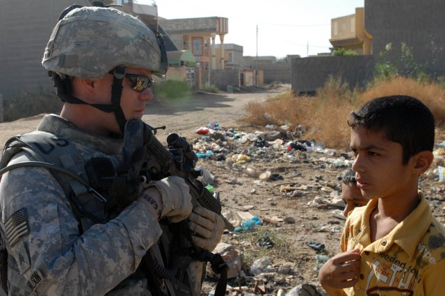 BAGHDAD - Austin, Texas native, Sgt. Joel Nicholson, an infantryman assigned to 1st Brigade Combat Team, 1st Cavalry Division, talkes to a local boy during a patrol, Nov. 7, in Tarmiyah.