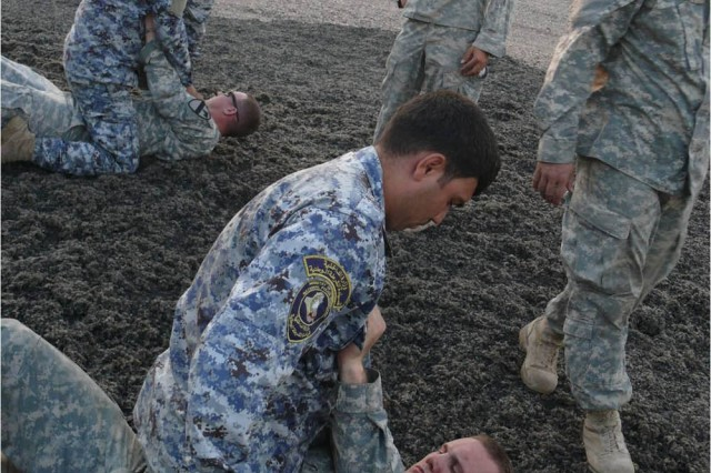 BAGHDAD - Pittsburg, Penn. native Spc. Nathan Lohr (on the ground), a cavalry scout from 1st Brigade Combat Team, 1st Cavalry Division, practices a straight-arm bar submission hold with an Iraqi Federal Policeman during a non-lethal force class held at Joint Security Station Istiqlal.