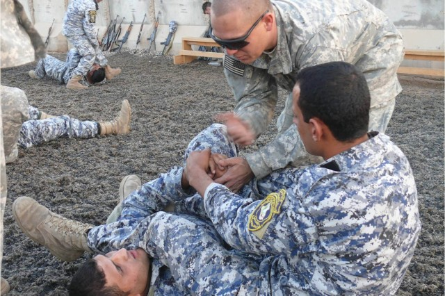 "BAGHDAD - ""You have to create tension for this to work,"" San Benito, Texas, native 1st Lt. Mike Olvera tells an Iraqi policeman during combatives training on Joint Security Station Istiqlal."