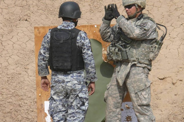JSS ISTIQLAAL, Iraq - Clovis, Calif. Native, Staff Sgt. John Hall (right), a cavalry scout with 1st Brigade Combat Team, 1st Cavalry Division, explains the need for a tight shot group to an Iraqi Federal policeman at Joint Security Station Istiqlal.