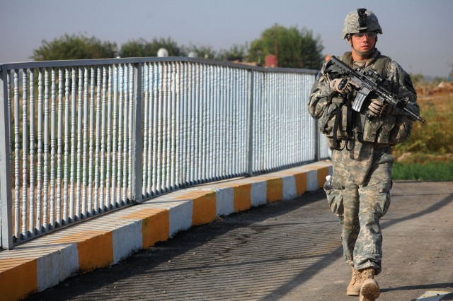 TAJI, Iraq - Evansville, Ind. native, Pfc. Travis Conder, an armor crewman attached to the 1st Brigade Combat Team, 1st Cavalry Division, walks across the Sheik Abdullah Bridge during a final inspection in Taji, Nov. 10. The bridge offers a faster and safer route to local markets for residents of the rural area.